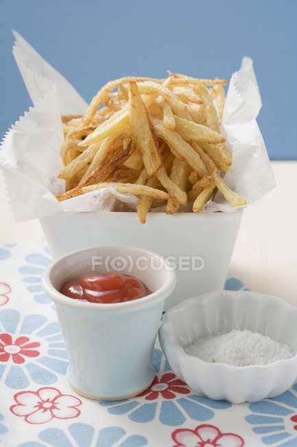 Patatas fritas en plato con salsa de tomate y sal - foto de stock