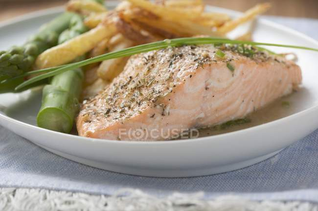 Salmon fillet with chips and green asparagus — Stock Photo