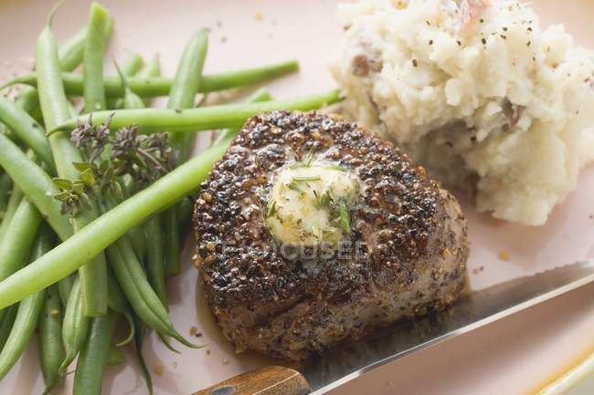 Peppered steak with herb butter — Stock Photo