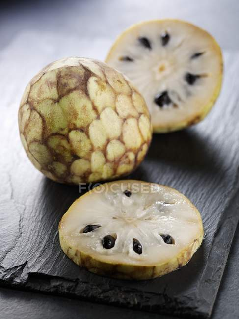 Fresh whole and sliced Cherimoya fruits — Stock Photo