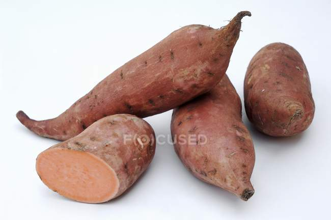 Whole and halved Sweet potatoes — Stock Photo