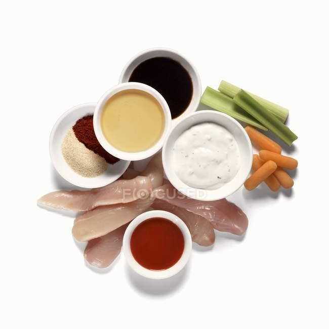 Pollo crudo con condimenti e verdure su superficie bianca — Foto stock