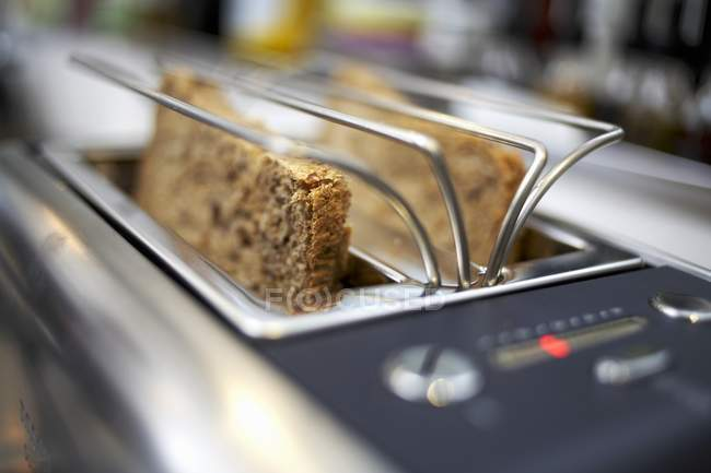 Closeup view of wholemeal bread slices in a toaster — Stock Photo