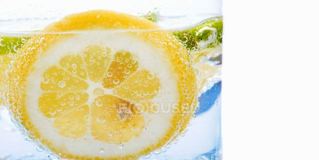 Glass of water with lemon slices — Stock Photo