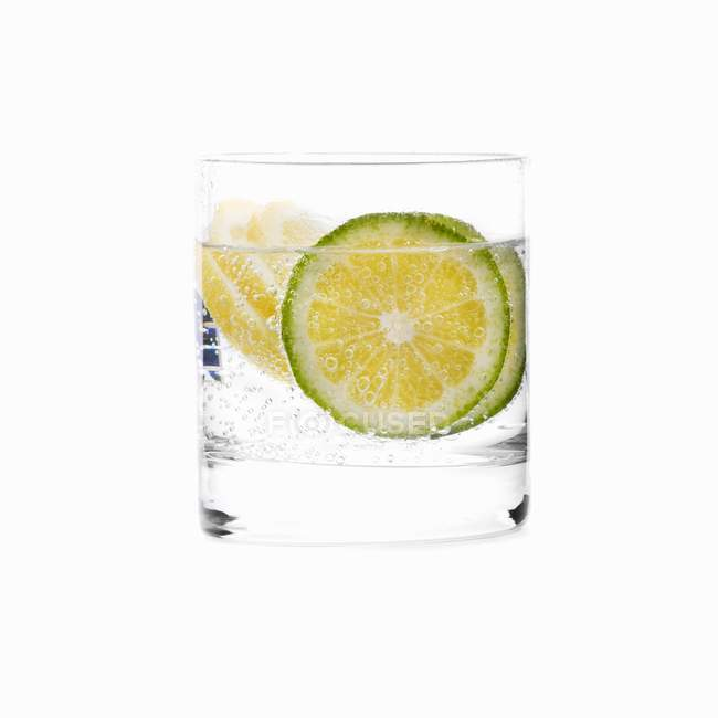 Glass of water with lime slices — Stock Photo