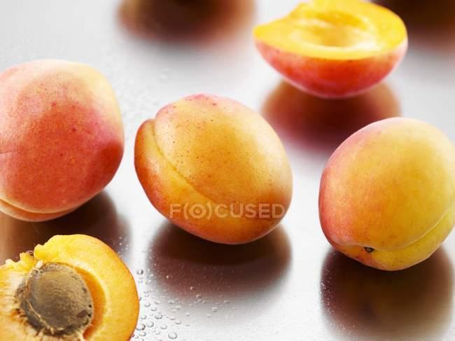 Несколько абрикосов, целый и половинки — стоковое фото