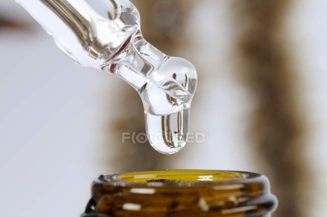 Closeup view of dripping liquid from pipette to bottle — Stock Photo