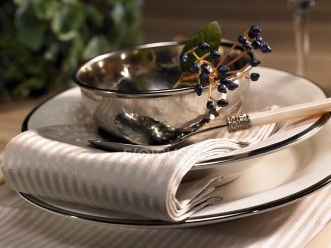 Un lugar festivo con un tazón de plata y bayas - foto de stock