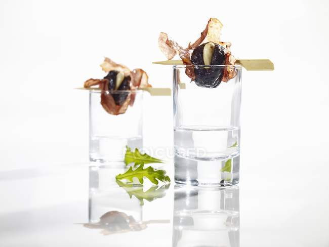 Closeup view of grilled plums wrapped in salami on glasses — Stock Photo