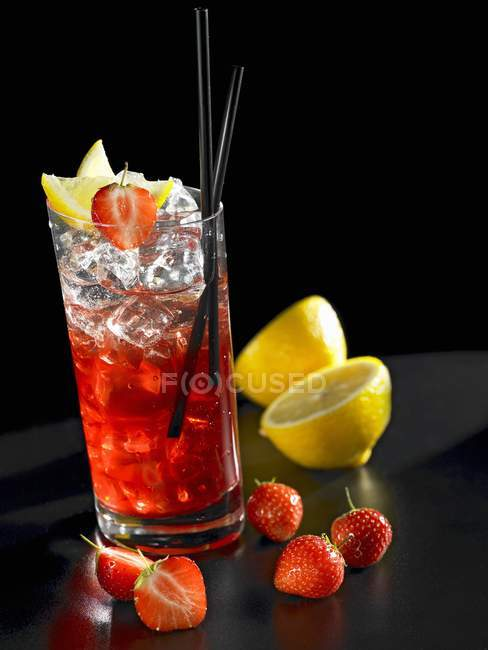 Closeup view of strawberry cocktail with lemons and ice cubes — Stock Photo