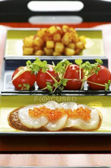 Vista de primer plano de la papa Masala con vieira Sashimis y tomates - foto de stock
