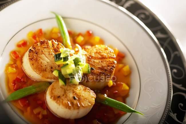 Capesante di mare sezionate con fagioli verdi e salsa d'arancia su piatto bianco — Foto stock