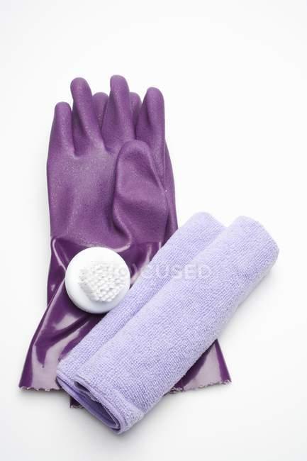 Primo piano vista di guanti di gomma viola con spazzola e asciugamano sulla superficie bianca — Foto stock