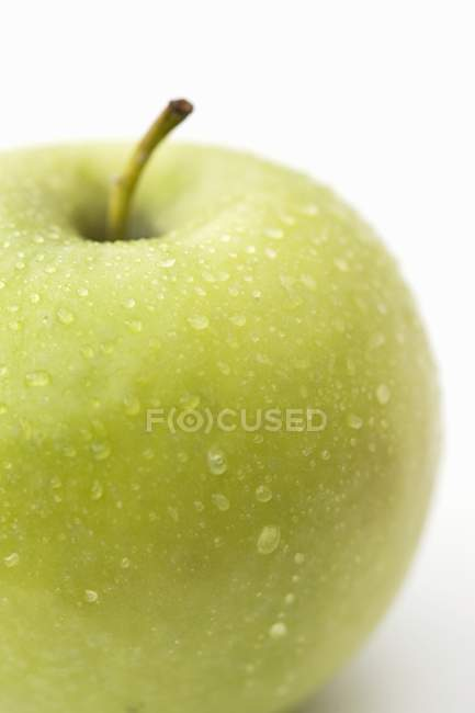 Green apple with drops of water — Stock Photo