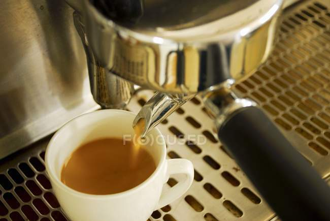 Zubereitung von Espresso in der Tasse mit Kaffee aus dem Automaten — Stockfoto