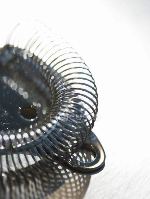Vue rapprochée de la passoire à cocktail métallique sur surface blanche — Photo de stock