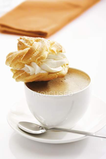 Profiterole on cup of coffee — Stock Photo