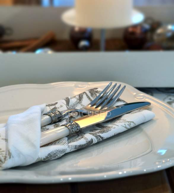 Knife and fork in a patterned napkin on a plate — Stock Photo