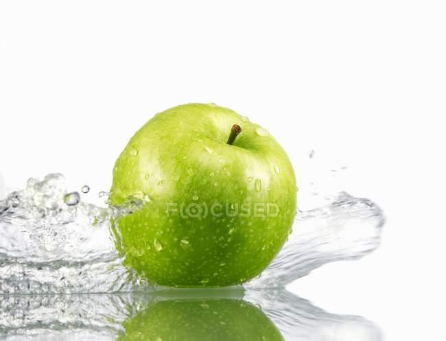 Green apple with splashing water — Stock Photo