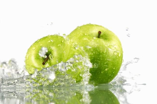 Два зеленых яблока с брызгами воды — стоковое фото