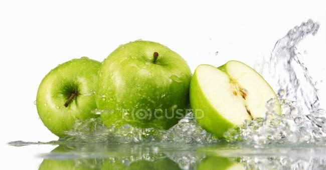 Зеленые яблоки целые и наполовину — стоковое фото
