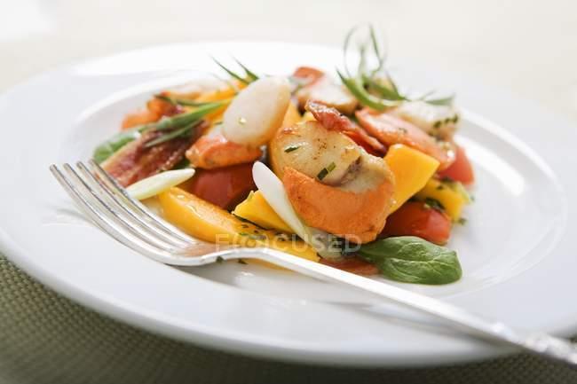 Vista ravvicinata di insalata di capesante fruttata e forchetta su piatto bianco — Foto stock