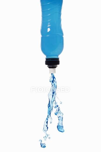 Vista de perto da bebida de energia azul esguichando para fora da garrafa — Fotografia de Stock