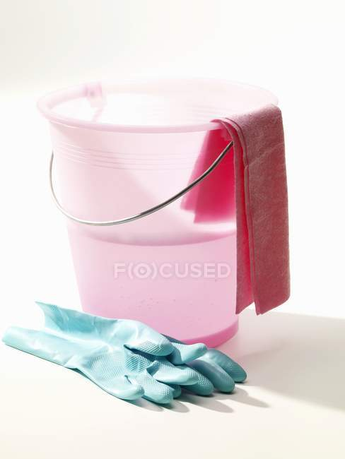 Pink cleaning bucket with water and rubber gloves — Stock Photo
