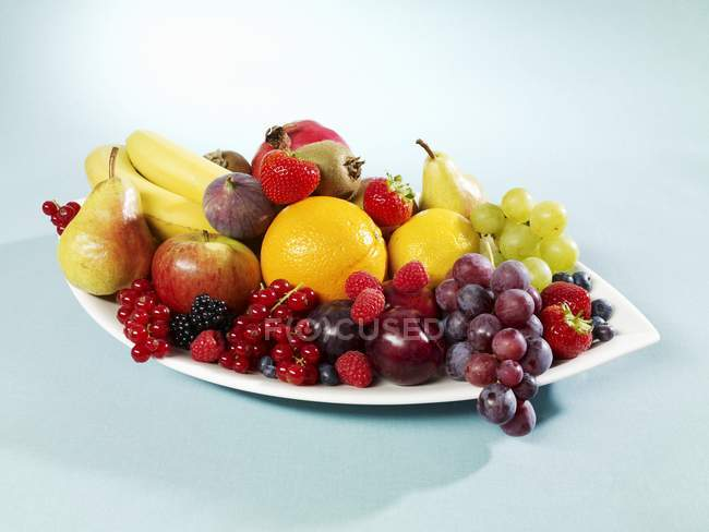 Fruits and berries on oval plate — Stock Photo