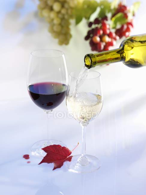 Pouring white wine into glass — Stock Photo