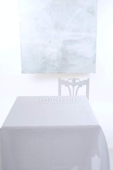 Пустой стол с белой скатертью, стулом и потрепанной доской на стене — стоковое фото