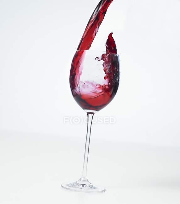 Verter vino tinto en una copa - foto de stock
