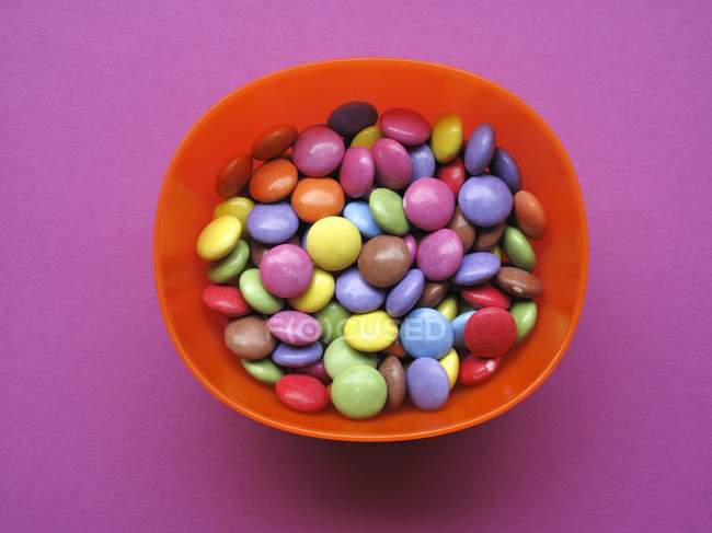 Closeup top view of colored chocolate beans in red bowl — Stock Photo