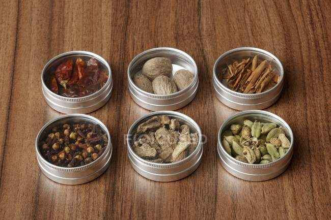 Assorted spices in small tins on wooden surface — Stock Photo