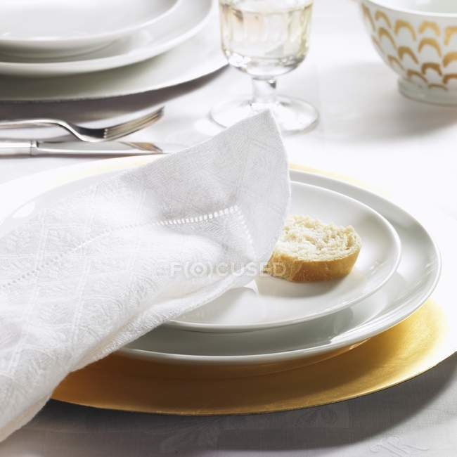 Festive place setting with fabric napkin and slice of baguette — Stock Photo