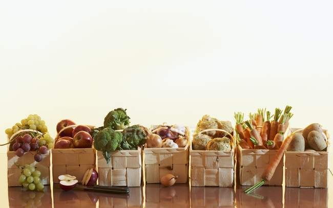 Fruit and vegetables in baskets over wooden surface on white background — Stock Photo