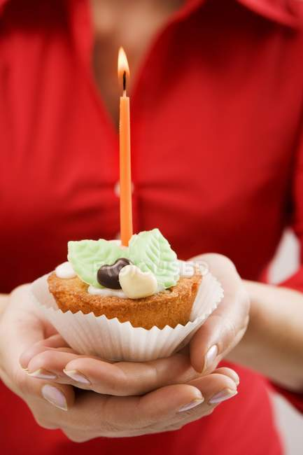 Woman holding cupcake with candle — Stock Photo