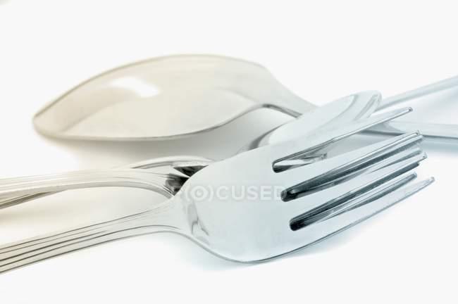 Vista closeup colheres e garfos na superfície branca — Fotografia de Stock