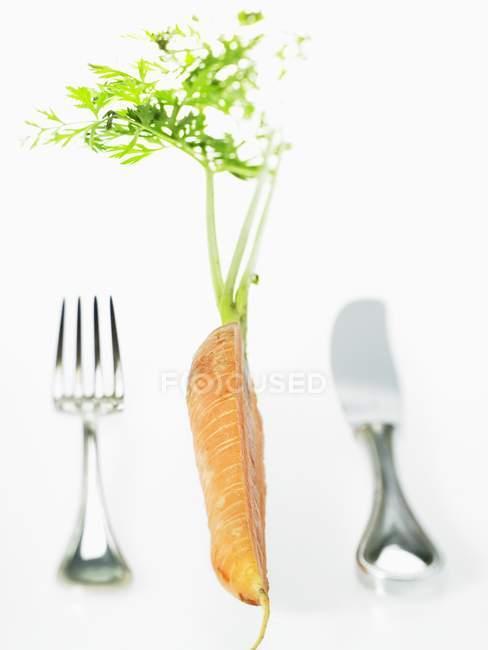 Die Hälfte der Karotten mit Messer und Gabel — Stockfoto