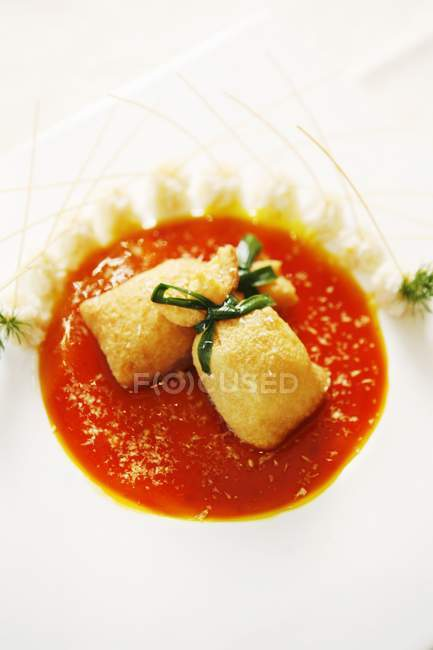 Closeup view of buns tied with herb on red sauce and white dish — Stock Photo