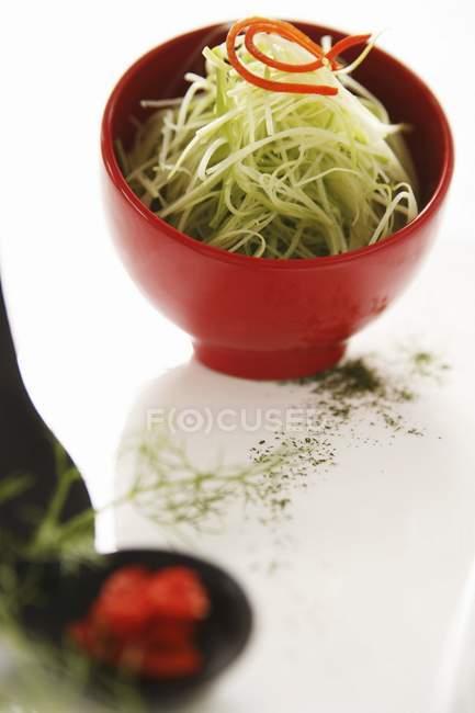 Ensalada de brotes de bambú en tazón rojo sobre superficie blanca - foto de stock