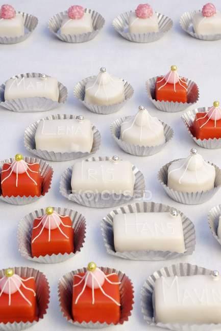Vermelhos e brancos petit fours em caixas de papel — Fotografia de Stock