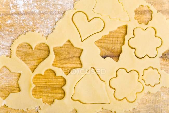 Vista superior de la masa de galletas con galletas cortadas - foto de stock