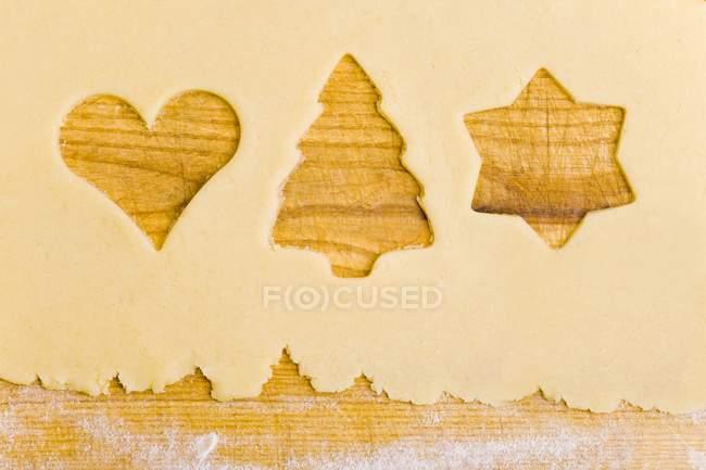 Primer plano vista superior de la masa de galletas con las formas de las galletas cortadas - foto de stock