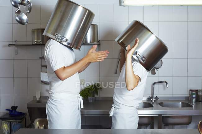 Two chefs having discussion with large pans on heads — Stock Photo