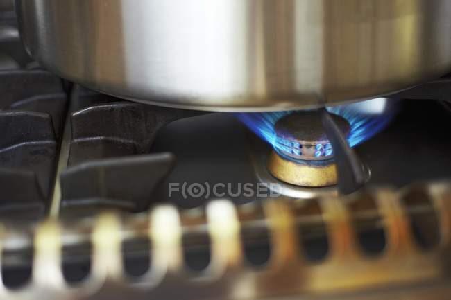 Closeup view of burning flame on a gas stove hob under a pot — Stock Photo