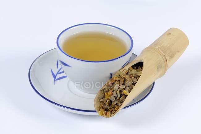 Radice di curcuma con una tazza di tè — Foto stock