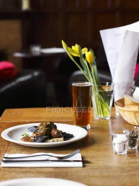 Підвищені зору обід з пива та квітами на стіл ресторан — стокове фото