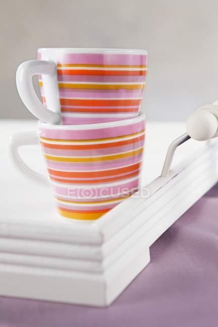 Detailansicht von zwei gestreiften Tassen auf weiße Tablett — Stockfoto