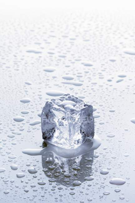 Closeup view of an ice cube on a wet surface — Stock Photo